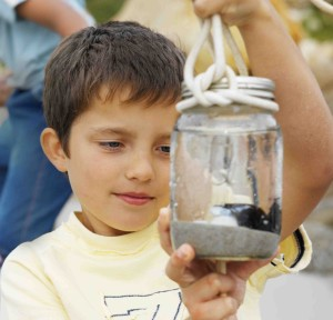 boy looking at insect in glass jar
