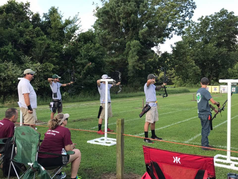 youth participating in archery at the shooting sports tournament